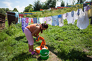 "Emelia, 26 years old is washing clothes in front of her house. She has all together four children and  lives for almost 9 years in the settlement. Mrs. Emelias opinion about the wall and the time before and after it was built: ""The difference is big - children were going there before but not anymore - now it is calm. They were playing and stealing there, not anymore. Good. Just the children were going there. We walk everywhere like we did before the wall was built."""