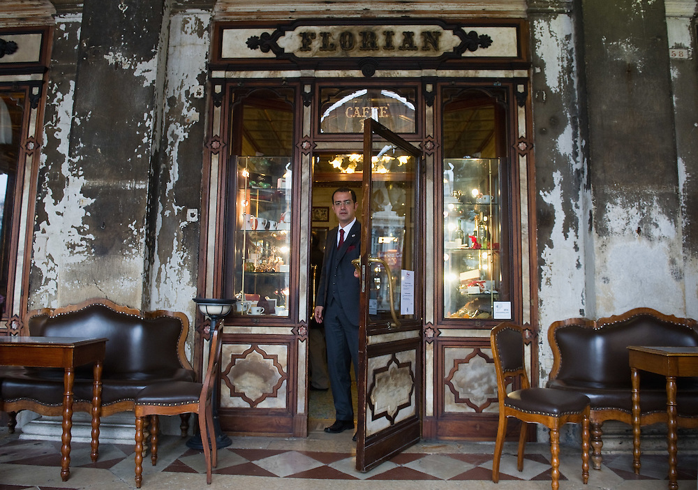 VENICE, ITALY - DECEMBER 02: The Manager of Caffe Florian opens the door facing the gallery and St Mark's Square on December 2, 2011 in Venice, Italy.The Venetian coffee houses have a  long standing history, established at the beginning of 1700 around St. Mark Square have been the centre of cultural meeting and innovations for centuries and served customers like Dickens, Goethe, Casanova and Lord Byron. San Marco is one of the six sestieri of Venice, lying in the heart of the city.