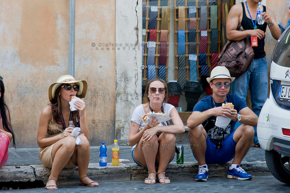 Roma 18 Luglio 2013<br /> Turisti mangiano pizza e panini  seduti per strada, vicino Fontana di Trevi a Roma<br /> Tourists eat pizza and sandwiches sitting on the street, near the Trevi Fountain in Rome