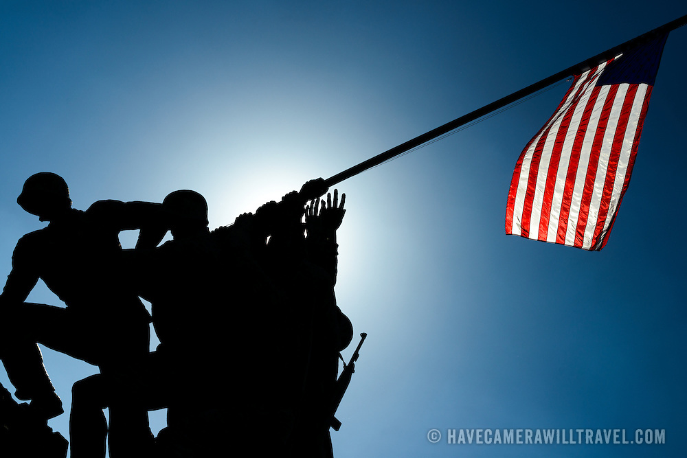 Backlit silhouette of the statue and American flag of the Iwo Jima Memorial (formally the Marine Corps War Memorial) in Arlington, Virginia, next to Arlington National Cemetery. The monument was designed by Felix de Wledon and is based on an iconic Associated Press photo called the Raising the Flag on Iwo Jima by Joe Rosenthal. It was dedicated in 1954.