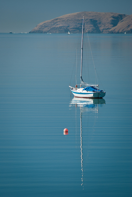 A yacht is moored in calm waters off Governors Bay, New Zealand, with Banks Peninsula in the distance