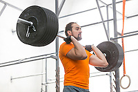 Confident man looking away while lifting barbell in crossfit gym