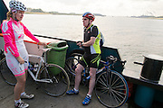 Twee wielrenners staan op de veerpont tussen Maassluis en Rozenburg.<br />