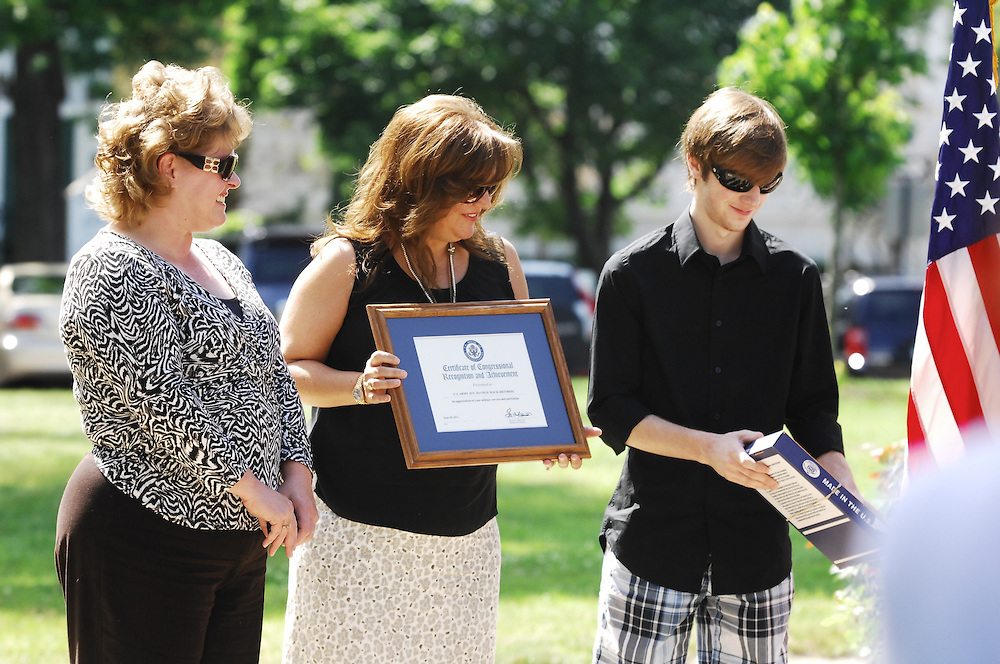 LAURA FONG TORCHIA - Sgt. Hack's wife Lani Hack of Hudson, is presented with a declaration of the Ceremony, their son Brenton is presented with a flag that had been flown at the Nation's Capital.