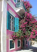 dark pink house, blue shutters, dark pink bougainvillea flowers, cobblestone street