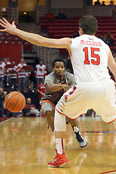 17 December 2014:  Deville Smith passes under the arm of Justin McCloud during an NCAA Men's Basketball game between the Skyhawks of University of Tennessee - Martin and the Redbirds of Illinois State at Redbird Arena in Normal Illinois