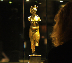 A Christie's employee looks at a  Roman bronze Isis-Aphrodite circa 2nd century AD estimated at £25,000-35,000 at the Antiquities at Christie's  pre auction display in London, England. Monday, 21st October 2013. Picture by Max Nash / i-Images