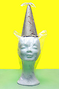 mannequin head covered with clear plastic wearing a metal cone as hat