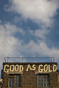 The words Good as Gold are written on the top of a Victorian building in Southwark, south London.