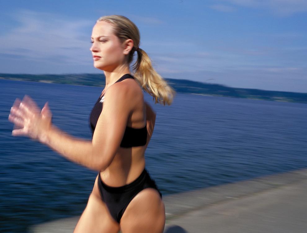 Woman runs along Lake Washington in Seattle, WA