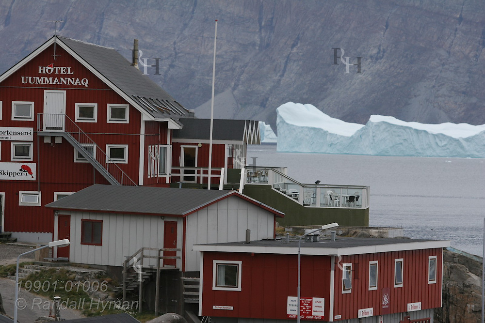 Colorful, Danish-style Uummannaq Hotel and shop buildings cling to rocky slopes overlooking icebergs and fjord at island town of Uummannaq, Greenland