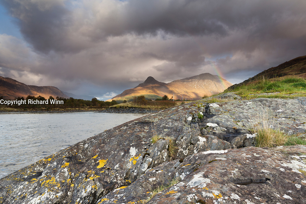 Rainbow arcing over the Pap of Glencoe or Sgorr na Ciche during unsettled weather, with granite and Loch Leven in the foreground.