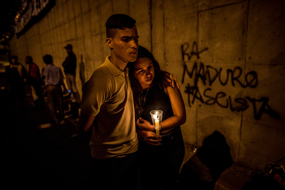 "CARACAS, VENEZUELA - JUNE 8, 2017: Members of ""The Resistance"" light candles and construct a makeshift memorial around the blood-stained spot on the road where anti-government protester Neomar Lander, 17, was killed by security forces during a protest in Caracas. Johan Caldera, a close friend of Mr. Lander said he is even more determined to protest since his friend was killed.  ""Now, I have no fear - because I already lost the fear I had, and the respect for the military. The little respect I had, is gone. Now, the real soldiers of Venezuela wear rags on their faces, they wear a glove and they they don't use grenades - they use stones, they use their will, and they use their balls to go out into the street."" He said he had discussed with Neomar the possibility of being killed during the protests, ""and he [Neomar] told me: brother, if I die - if I lose my life during a protest, I don't want everyone to stop marching, I want them to march double and keep going to the street for a week, every single day, day and night without fear.""  PHOTO: Meridith Kohut"