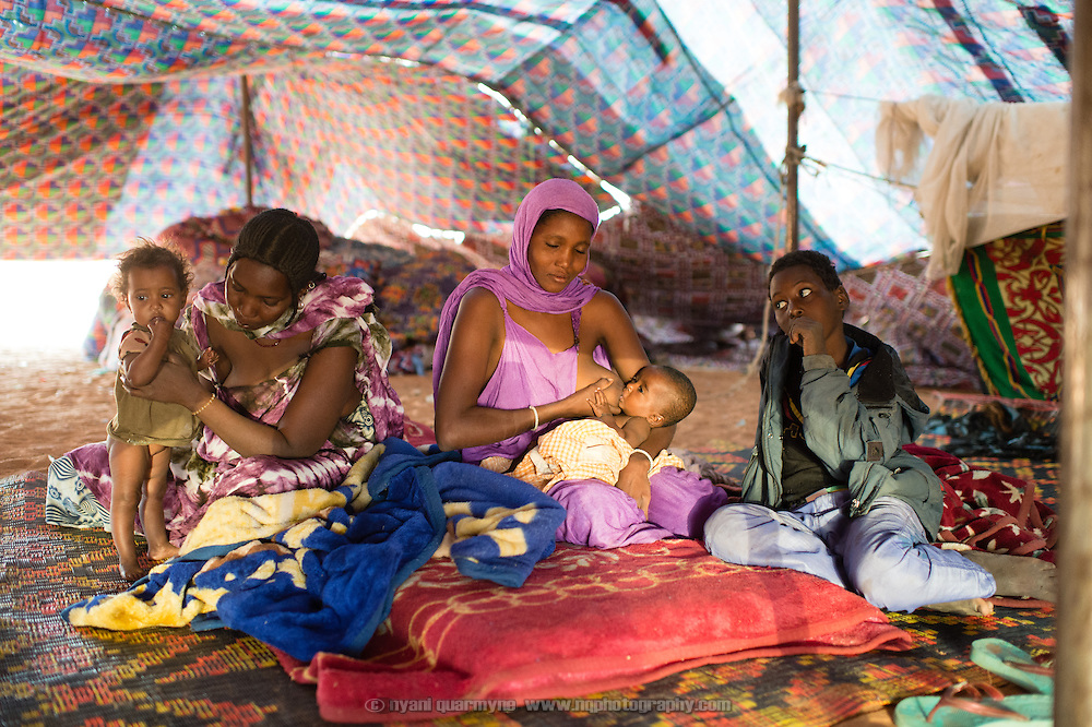 Mothers, wives of the same husband, with their children soon after waking up at the Mbera camp for Malian refugees in Mauritania on 2 March 2013.