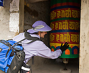 "In the Everest Area of Nepal, Asia: A prayer wheel (called mani chos-'khor or Mani wheel by the Tibetans) is a wheel on a spindle made from metal, wood, leather, or coarse cotton. On the wheel are written or encapsulated prayers or mantras. According to the Tibetan Buddhist belief, spinning such a wheel will have much the same effect as orally reciting the prayers. A prayer wheel symbolizes ""turning the wheel of Dharma,"" which describes the way in which the Buddha taught."