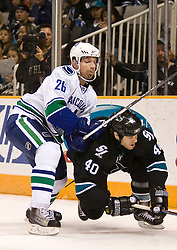 April 8, 2010; San Jose, CA, USA; Vancouver Canucks right wing Mikael Samuelsson (26) checks San Jose Sharks defenseman Kent Huskins (40) during the first period at HP Pavilion.  San Jose defeated Vancouver 4-2. Mandatory Credit: Jason O. Watson / US PRESSWIRE