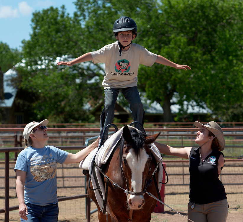 gbs050717p/LIVING -- Ellen Parker of Rio Rancho, left, and Tasha Books, horse vaulting instructor spot Matthew Fehr as he stands on a walking Kirby Jack during the  Cloud Dancers of the Southwest Therapeutic Horsemanship Program. (Greg Sorber/Albuquerque Journal)