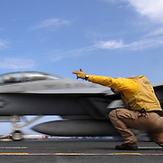 "LCDR Alan D'Jock ducks into his shoot stance as an F/A-18F Super Hornet from the ""Swordsmen"" of Strike Fighter Squadron THREE TWO (VFA 32) speeds past while launching from catapult number one during flight operations on board the Nimitz-class aircraft carrier USS Harry S. Truman (CVN 75)."