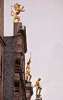 Golden statues of a lion and figures on a rooftop in Antwerp, Belgium.