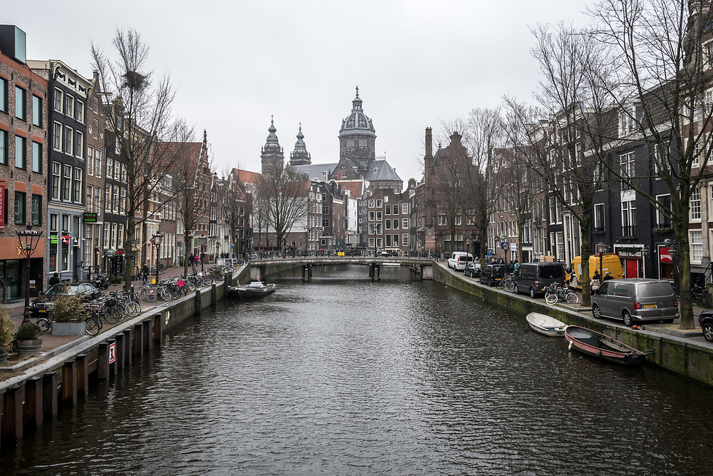 A canal runs through mainstreet with iconic narrow canal houses lining either side, Amsterdam Netherlands.