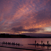 Two eight crews prepare to row during a beautiful sunrise on Lake Karapiro, near Cambridge, Waikato. Many national and international rowing competitions are held on Lake Karapiro which is also the home of The Rowing New Zealand High Performance Centre. Lake Karapiro hosted the 2010 World Rowing Championships. Lake Karapiro, Waikato,  New Zealand. 15th December 2010. Photo Tim Clayton