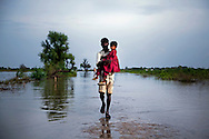 A man carries a child through rising floodwaters, on 11 September, 2011, in Mirpurkhas, Pakistan. More than 17% of children in the flood areas are severely acutely malnourished and 67% of livestock has been destroyed after torrential monsoon rains, reminiscent of the 2010 floods that devastated Pakistan, have reportedly already killed over 200 people, left 300,000 homeless and affected over 7 million. (Photo by Warrick Page)