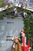Portrait of boy (7-9) in pirate costume and boy (5-6) in jaguar costume by shed