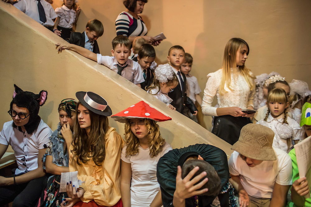 MARIUPOL, UKRAINE - SEPTEMBER 1, 2015: First-year students at School 68 arrive for an assembly to welcome them on the first day of the new school year in Mariupol, Ukraine. On January 24 of this year, shelling in the same neighborhood killed 31 people, all civilians, and while much recent fighting has been concentrated near Mariupol, a drop in ceasefire violations in the past few days has been credited to a desire to not interfere with the start of the new school year. CREDIT: Brendan Hoffman for The New York Times