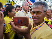 05 MAY 2104 - BANGKOK, THAILAND:  Anti-government leader SUTHEP THAUGSUBAN (center) is photographed by an anti-government protester at Sanam Luang in Bangkok. Thousands of Thais packed the area around Sanam Luang and the Grand Palace Monday evening for a special ceremony to mark Coronation Day, which honored the 64th anniversary of the coronation of Bhumibol Adulyadej, the King of Thailand. Many of the people also support the anti-government movement led by Suthep Thaugsuban. Most of the anti-government protesters are conservative supporters of the monarchy.   PHOTO BY JACK KURTZ