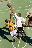 Young men reaching in air for basketball during game elevated view