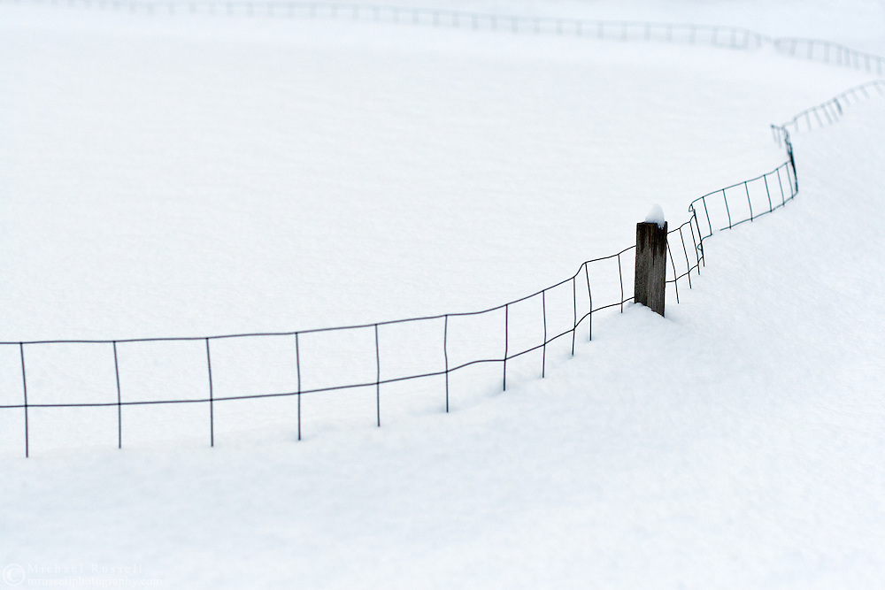 A fence is nearly covered in deep snow after a snow storm in the Fraser Valley of British Columbia, Canada