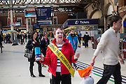 "A woman wearing a yellow sash ""Helping the Homeless"" is collecting money donations for a homeless charity from members of the public passing through London Victoria railway station. The train station is located in central London and is the second-busiest in the capital."