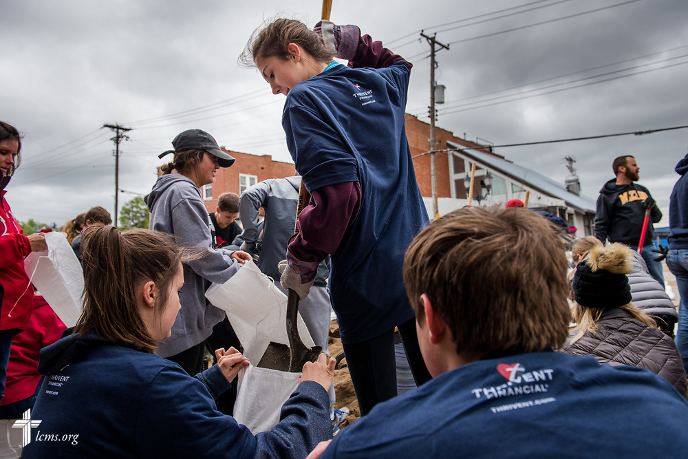 Madi Petry shovels sand into bags with the help of her sister Kati Petry and fellow volunteer Bradley Bisaga from St. Mark's Lutheran Ministries, Eureka, Mo., on Monday, May 1, 2017, in downtown Eureka. The group joined other volunteers to help keep rising flood waters out of local businesses. LCMS Communications/Erik M. Lunsford