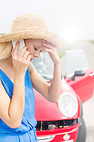 Tensed young woman using cell phone by broken down car