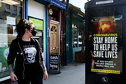© Licensed to London News Pictures. 09/04/2020. London, UK. A woman wearing a face mask looks at a coronavirus public information campaign billboard in north London, which says 'STAY HOME TO HELP US SAVE LIVES.' during the pandemic outbreak of the COVID-19 virus. Photo credit: Dinendra Haria/LNP