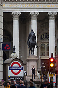 A men makes a call beneath the Equestrian statue of the Duke of Wellington at Bank Underground station on Cornhill in the City of London, the capital's financial district (aka The Square Mile), on 26th March, 2018, in London, England.