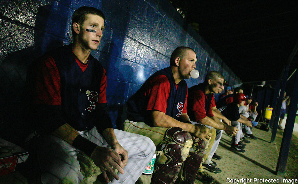 Seve Alvarez, left, and a bubble-blowing catcher Garrett Campfield study the game from the team's dugout during one of theClarinda A's at-bats during their July meeting with the Omaha Diamond Spirit.  photo by David Peterson