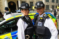 London, July 8th 2017. Thousands of LGBT+ revellers take part in the annual Pride in London parade under the banner #LoveHappensHere. PICTURED: Met police officers sport pride colours on their epaulettes, with a police car decked out in appropriate colours behind them..