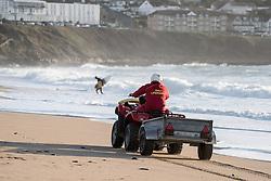 A RNLI lifeguard patrolling Fistral Beach in Newquay, Cornwall.