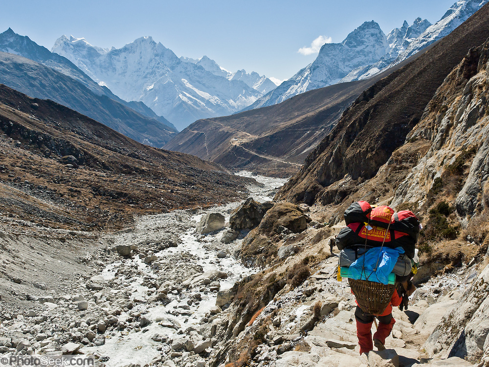 "A heavily loaded porter descends from Gokyo, along the Dudh Kosi (or Dudh Koshi, ""milky river"") in the Khumbu region of the Nepal Himalaya, in Sagarmatha National Park. Sagarmatha National Park was created in 1976 and honored as a UNESCO World Heritage Site in 1979."