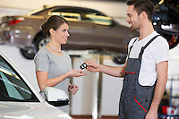 Happy repairman giving car key to woman in workshop