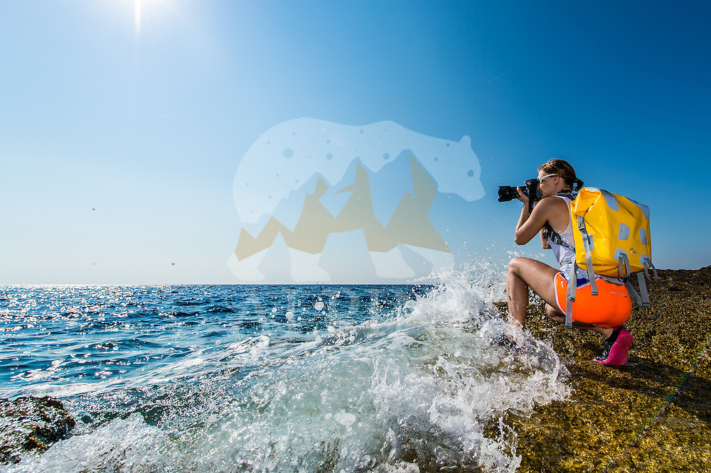A female photographer wearing a yellow waterproof backpack as seen on a sunny Summer day photographing on the coast line of Croatian natural park of Premantura.