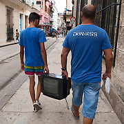 Cubans manage their daily life whether  waiting for overcrowded busses or doubling up on old classic cars and motorcycles or walking everywhere. Locals and tourist walk and window shop in La Habana Vieja. <br />