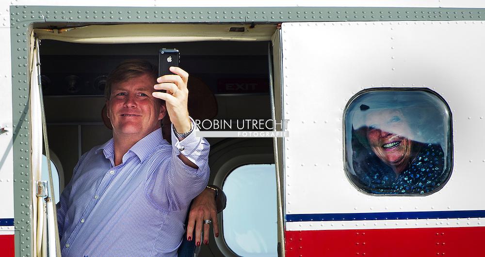 SABA - Prins Willem-Alexander maakt een foto met zijn telefoon al hij met prinses Maxima en koningin Beatrix (R) vertrekt van Saba. Het koninklijk gezelschap brengt een tiendaags bezoek aan het Caribisch deel van het koninkrijk. ANP ROYAL IMAGES ROBIN UTRECHT