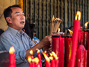 16 SEPTEMBER 2016 - BANGKOK, THAILAND: A man prays at Heng Chia Shrine on Chareon Krung Road during the Mid-Autumn Festival in Bangkok. The festival was originally a time to enjoy the successful reaping of rice and wheat and is still celebrated as a harvest festival in agricultural communities. In Bangkok, people make food offerings in honor of the moon. And it is an opportunity to share mooncakes.   PHOTO BY JACK KURTZ
