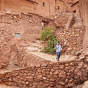 A young boy walks down the steep steps in the Ksar (a group of earthen buildings)of Ait Benhaddou. He is one of the few children remaining in this World Heritage Site.