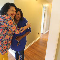 Ketra Ruff, left, gives Kimberly Jeter a congratualtory hug from before Jeter's home is dedicated Friday morning.