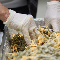 Green bean casseroles are prepared by volunteers for the Salvation Army's community wide Thanksgiving dinner.