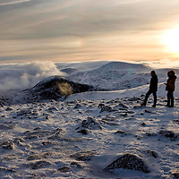 The sun sets above the Cairngorms in this view taken from the summit of Cairn Gorm (1245m) looking towards a cloud shrouded Coire Cas.<br />