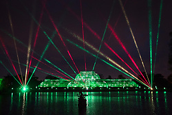© Licensed to London News Pictures. 21/11/2017. London, UK. Lasers fill the sky above the Palm House to herald the opening of Christmas at Kew at Royal Botanical Gardens, Kew. The spectacular displays are illuminated by over one million tiny twinkling lights placed all over Kew Gardens - open Wednesdays – Sundays from 22 November 2017 – 2 January 2017. London, UK. Photo credit: Peter Macdiarmid/LNP